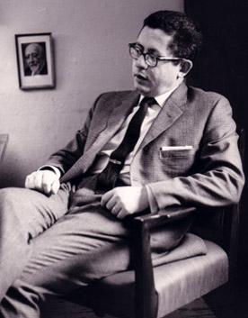Rabbi Albert H. Friedlander with a portrait of Rabbi Leo Baeck on the wall behind him, 1955.