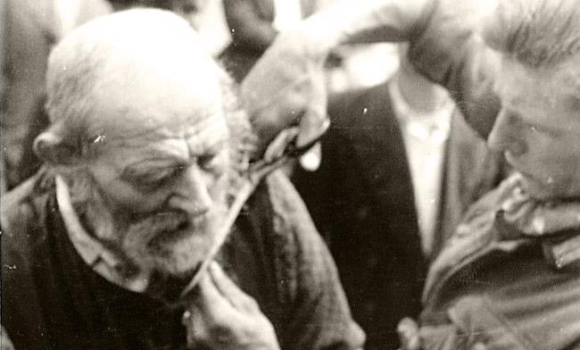 German soldier cutting a man's beard.